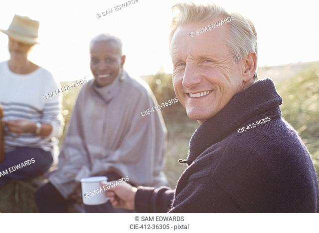 Portrait smiling senior man drinking coffee with friends on sunny beach
