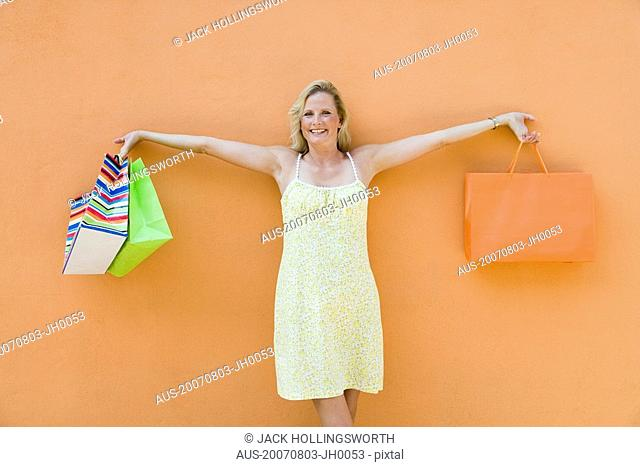 Mature woman holding shopping bags with her arm outstretched and smiling
