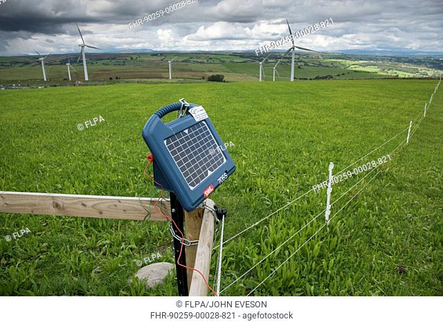 Solar powered electric fence unit on pasture, with wind turbines in background, Adfa, Newtown, Powys, Wales, September