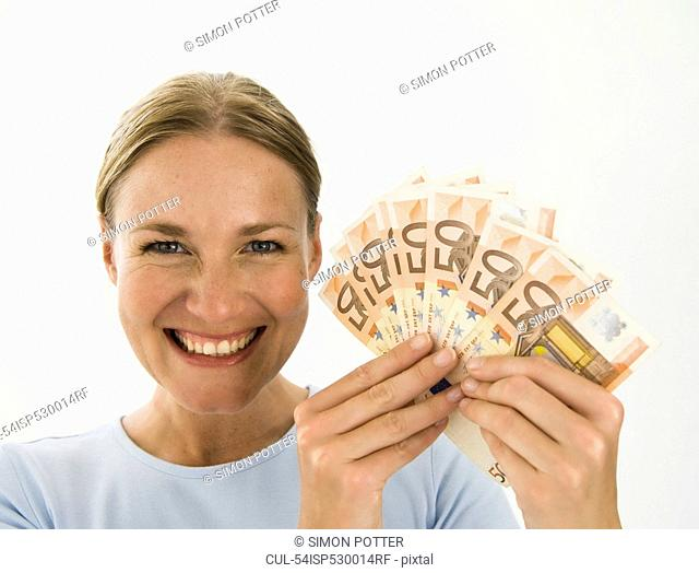 Smiling woman holding Euro notes
