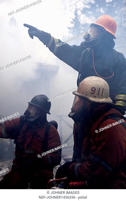 Three fire fighters in smoke