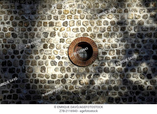 A circular window in a wall of the Retiro park of Madrid city