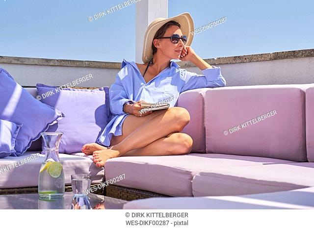 Woman with book relaxing on sun deck