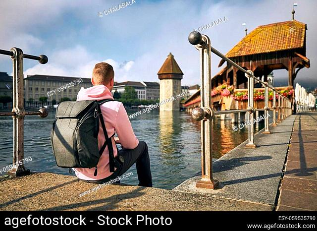 Young man sitting on waterfront and looking at Chapel Bridge in Lucerne, Switzerland