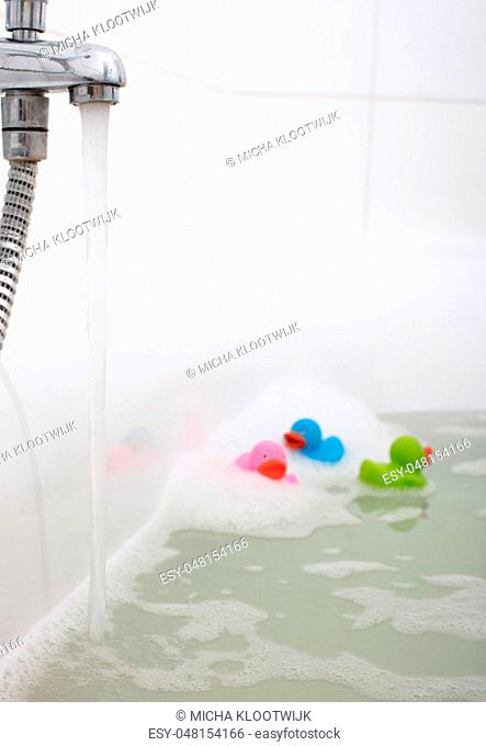 Pink, green and blue duck in a bathtub, surrounded by soap