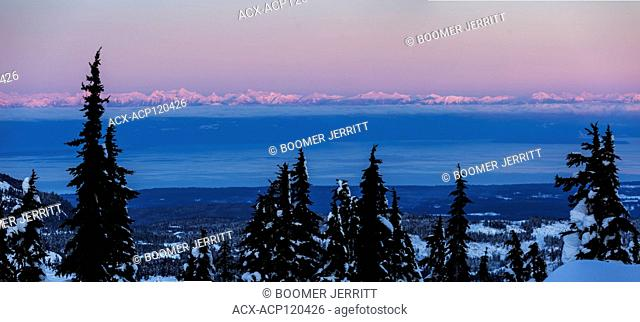 Cold color hues settle over a coastal forest with the British Columbia Coast Range and Georgia Strait in the background after sunset