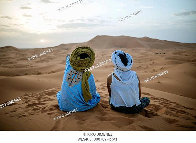 Woman sitting in the desert with Berber guide, watching sunset