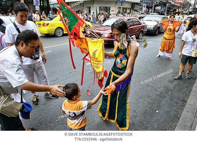 child making an offering to Vegetarian festival devotee in Bangkok, Thailand