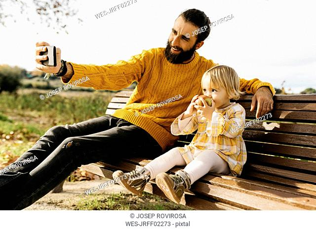 Father and daughter sitting on a bench in the park in autumn, father taking a selfie, daughter eating an apple