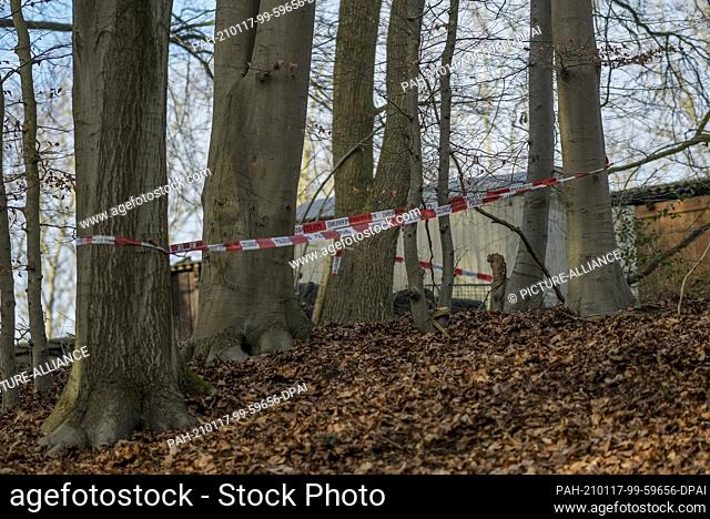 17 January 2021, Lower Saxony, Seevetal: Police tape is wrapped around several trees in a wooded area where there is also a trailer and a wooden hut