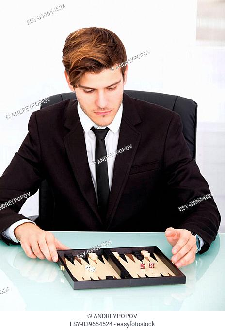 Handsome Businessman Playing Backgammon At Office Desk