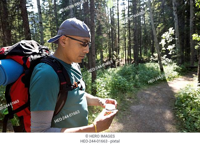 Backpacker checking compass on trail in woods