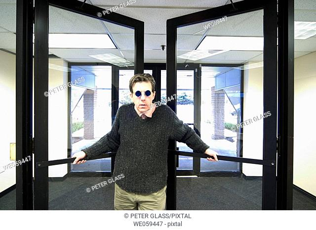Man in an office building, wearing blue sunglasses, holding open the lobby doors