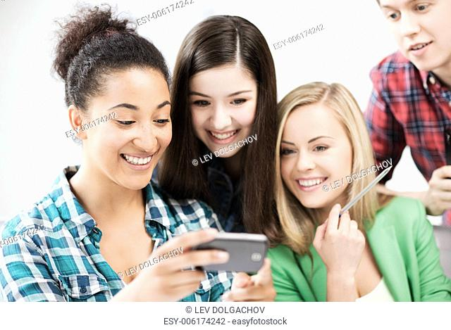 education and internet - smiling students looking at smartphone