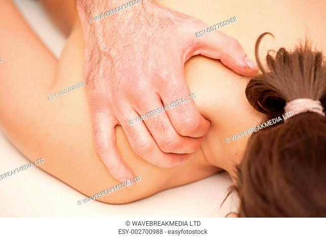 Chiropractor squeezing the shoulder of woman while massaging indoors