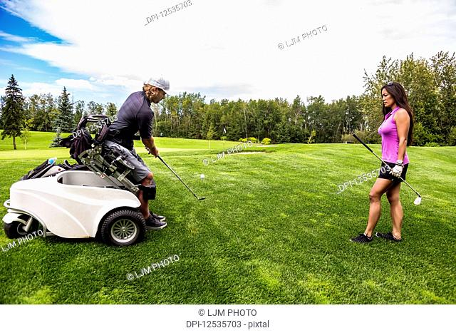 A physically disabled golfer, using a specialized wheelchair, hits the golf ball with his golf club on the golf green as a female golfer stands watching;...