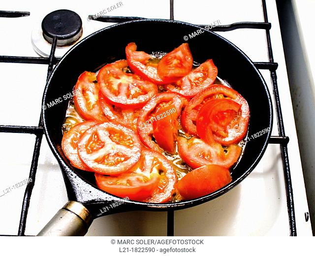 Gas stove. Tomatoes in a paella