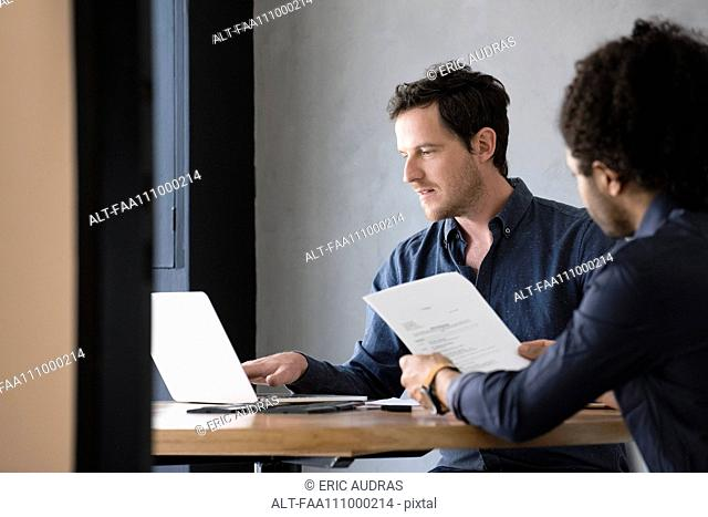 Man using laptop while other man reads document