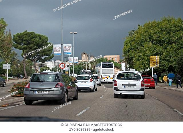 Rainy winter skies and cars in city traffic with Christmas light fixtures up in November 2011 in Palma de Mallorca, Spain