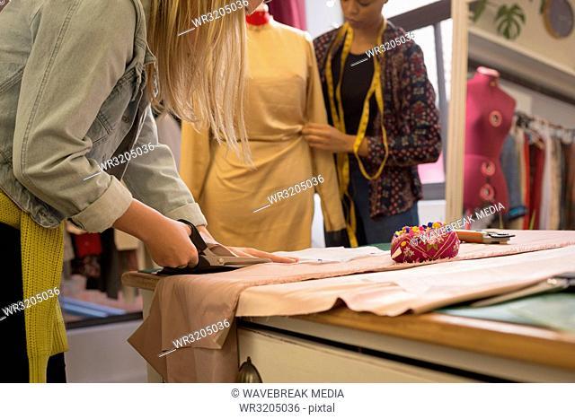 Fashion designer cutting fabric