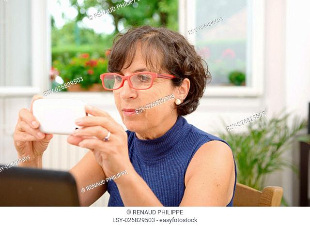 mature woman with red glasses and phone