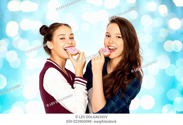 people, friends, teens and friendship concept - happy smiling pretty teenage girls with donuts eating and having fun over blue holidays lights background