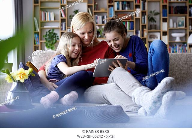 Mother and her daughters sitting on couch, having fun using digital laptop