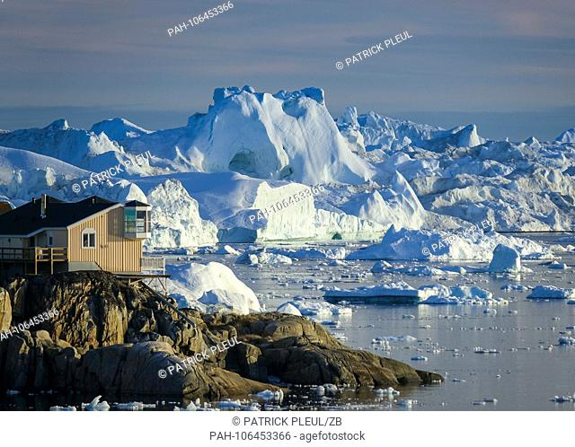 27.06.2018, Gronland, Denmark: Icebergs floating in the water off the coastal town of Ilulissat in western Greenland. The city is located on the Ilulissat...