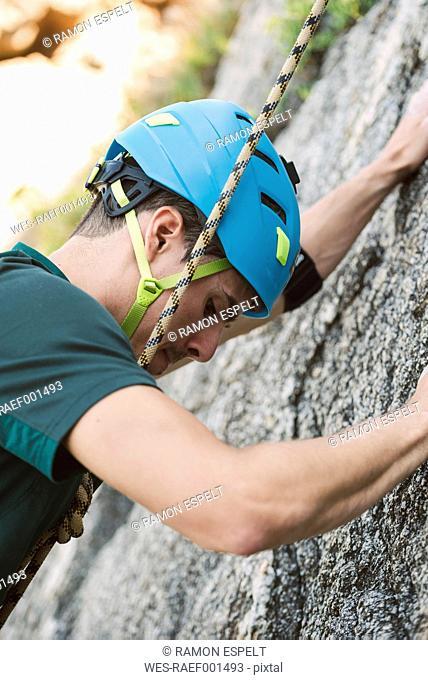 Close-up of young man climbing a rock wall