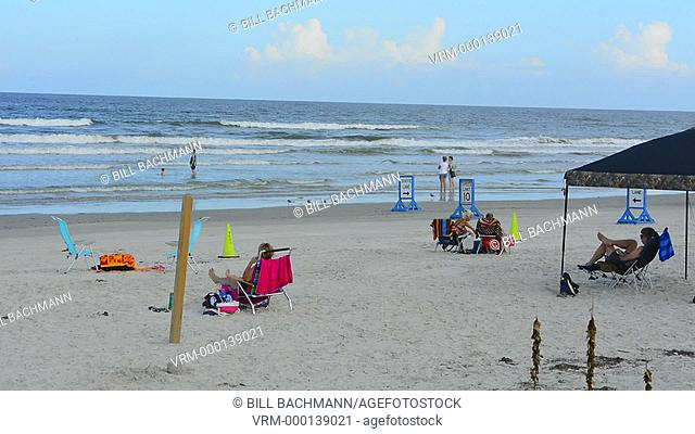 New Smyrna Beach Florida driving cars on beach traffic danger speed limits with familes playing and autos moving