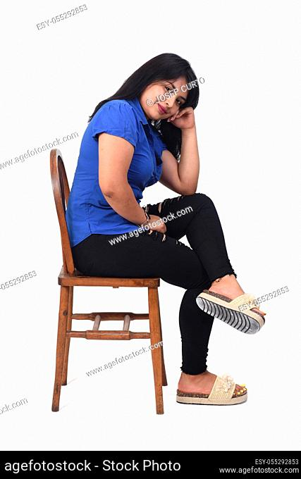 portrait of a latin woman sitting on a chair in white background, side view, looking at camera, arms crossed and hand on faece