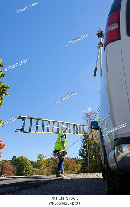 Engineer carrying a ladder to climb power pole