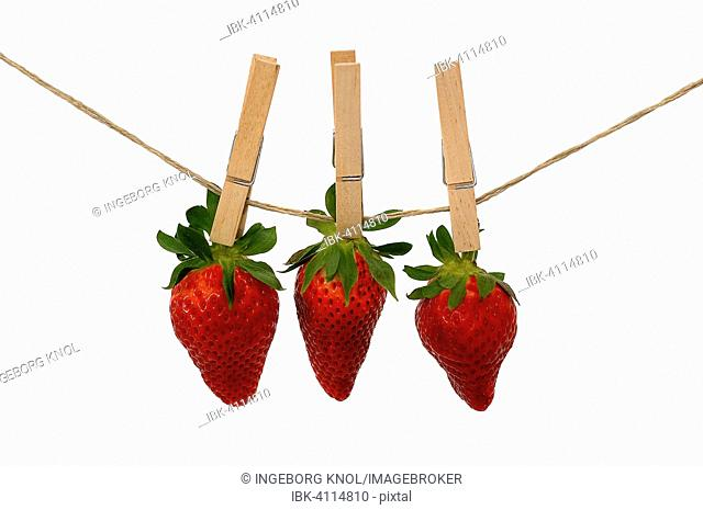Three strawberries with wooden clothespins on a line