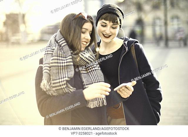 two women using smartphone, wearing leisure clothes, in city Cottbus, Brandenburg, Germany