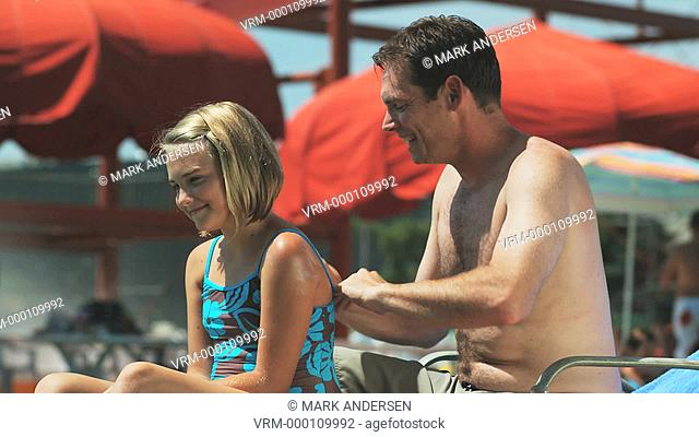 father putting sunscreen on daughter