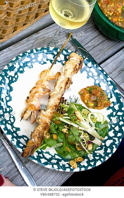 Gourmet chicken and shrimp shish kebab dinner with salad and wine served on rustic picnic table  Danbury Wisconsin USA