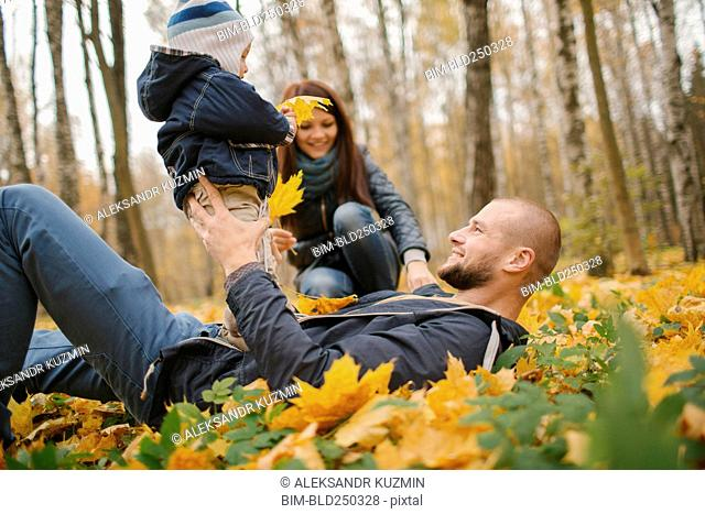 Middle Eastern father laying in autumn leaves holding baby son