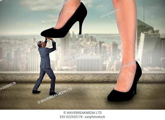 Composite image of businesswoman stepping on tiny businessman against balcony overlooking city