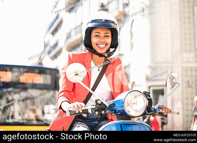 Portrait of happy young woman riding motor scooter in the city, Lisbon, Portugal