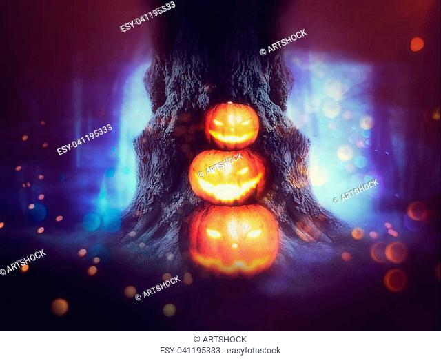 Big crooked spooky tree in the night forest with Halloween pumpkins