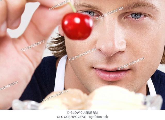Ice cream seller holding a cherry