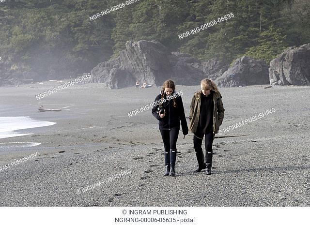 Tourist walking on beach, Pacific Rim National Park Reserve, Tofino, Vancouver Island, British Columbia, Canada
