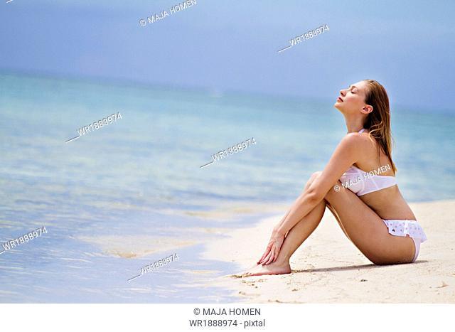Young woman in bikini relaxes on beach, Lankayan Island, Borneo, Malaysia