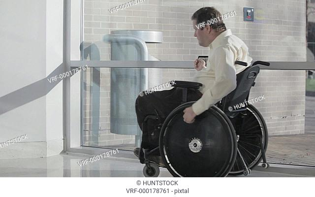 Man with spinal cord injury in wheelchair using automatic door opener to enter building
