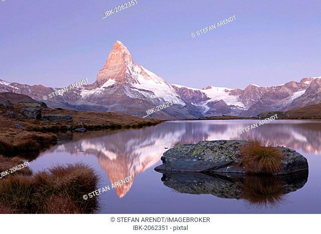 First morning light on Stellisee Lake overlooking Mt Matterhorn with reflections, Zermatt, Valais, Switzerland, Europe