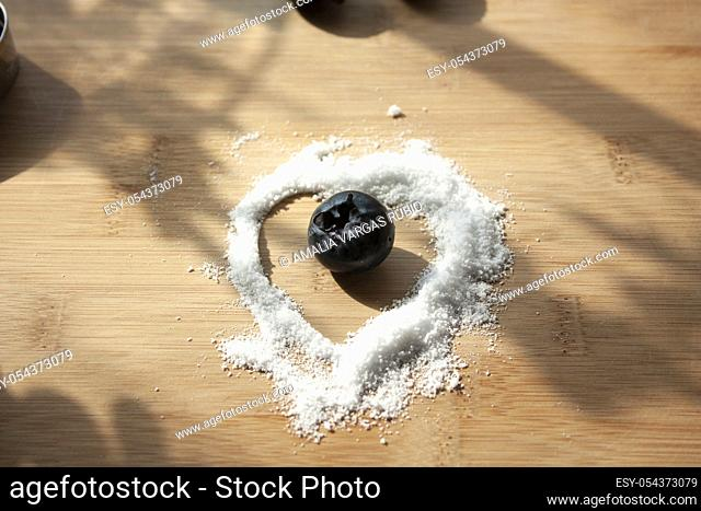 Heart of sugar free sweetener granules enclosing a blueberry on wooden board Mexico gourmet