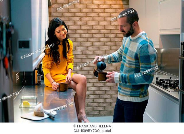 Hipster couple having coffee and talking in kitchen
