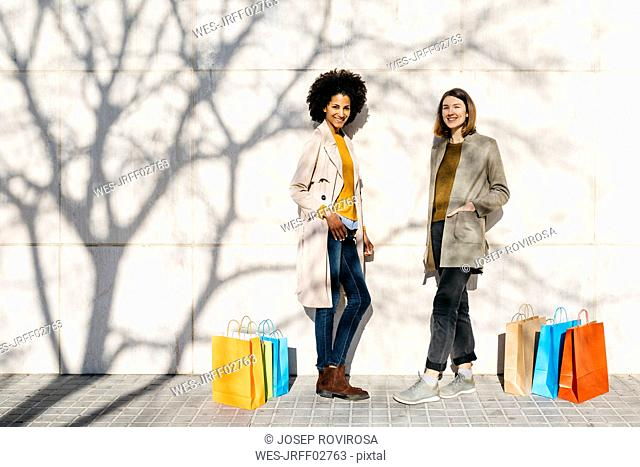 Portrait of two happy women with shopping bags standing at a wall