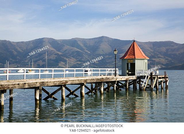 Akaroa Canterbury South Island New Zealand  Daly's Wharf with small red roof building at end of jetty and view across harbour in Bay