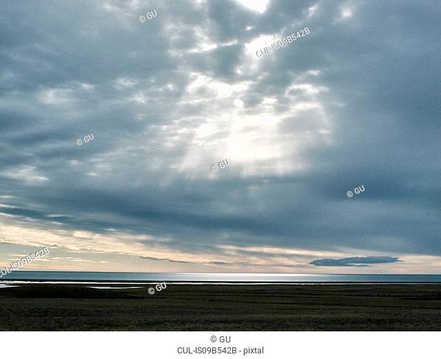 Sun beams from grey cloudy sky over sea horizon, Reykjavik, Iceland